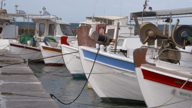 vídeos de stock e filmes b-roll de lockdown: colorful boats tied to a dock in naoussa rock gently in the waves - greece