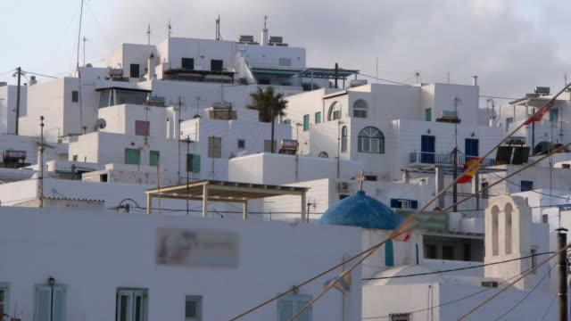 lockdown: cycladic buildings at sunset through the rigging of fishing boats - 顕花植物点の映像素材/bロール