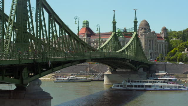 vídeos de stock e filmes b-roll de lockdown: ferries move on the danube under liberty bridge before architecture - ponte das correntes ponte suspensa