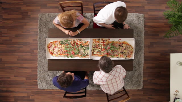 MS, Lockdown, four friends sitting down to eat pizza, overhead view