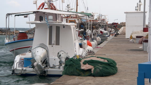lockdown: greek fishing boats bob in choppy water by a rock pier - fisherman stock videos & royalty-free footage