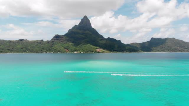 lockdown: jet skies moving across vibrant blue ocean with tall mountain behind in bora bora, french polynesia - フランス海外領点の映像素材/bロール