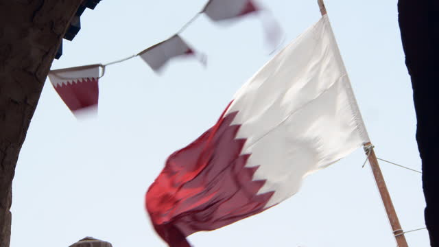 lockdown: large flag and pennants of qatar flutter furiously in a strong wind near stone building  - doha, qatar - qatar stock videos & royalty-free footage