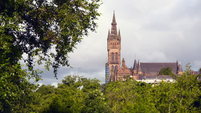 lockdown: large sandstone cathedral towers over lush green trees in sunshine - glasgow, scotland - temple building stock videos & royalty-free footage