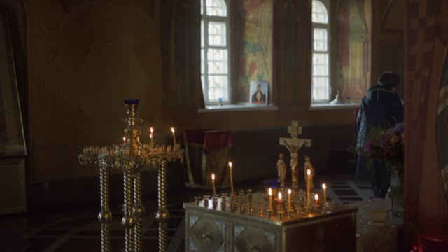 vidéos et rushes de lockdown: lone woman covered in warm clothes praying inside the chapel doing sign of the cross - irkutsk, russia - croix religieuse