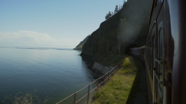 vidéos et rushes de lockdown: long train travelling by the beautiful lake and passing the tunnel of the mountain - lake baikal, russia - passer devant