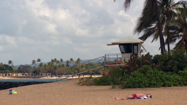 lockdown: man sunbathing near lifeguard tower: oahu - bagnino video stock e b–roll