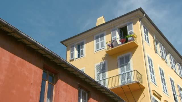 vídeos y material grabado en eventos de stock de lockdown: man working on an upper balcony of a picturesque building in nice - detalle arquitectónico exterior