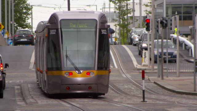 vidéos et rushes de lockdown: modern tram of dublin ireland passing the intersection - traverse city