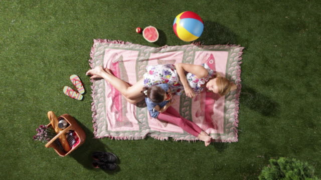 MS, Lockdown, mother and daughter relaxing on a blanket, eating apples, overhead view