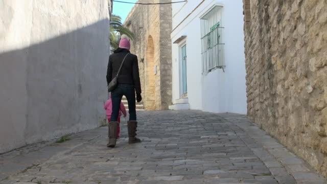 vídeos de stock, filmes e b-roll de lockdown: mother and kids walking on the street - paralelepípedo