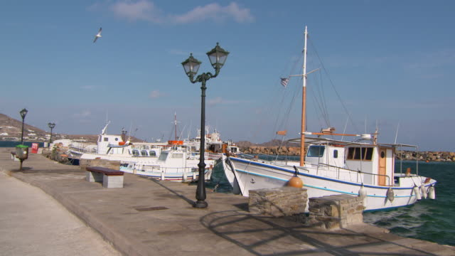 vídeos de stock e filmes b-roll de lockdown: naoussa harbor in golden sunlight with small boats and yachts - barco