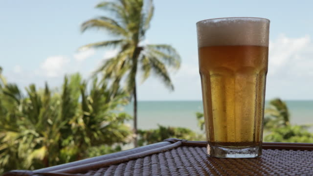 MS Lockdown of a glass of cold beer on a table and a beach in the background