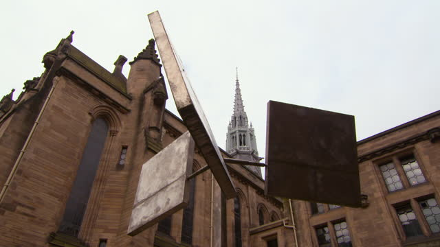 lockdown of a steel wind sculpture swaying in the breeze outside of glasgow university on a gray cloudy day - stone object stock videos & royalty-free footage