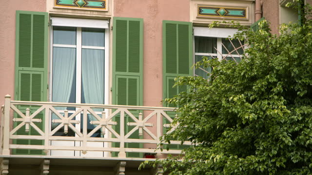vidéos et rushes de lockdown of a tall apartment window and balcony with a lush green tree in the foreground - monte carlo, monaco - volet