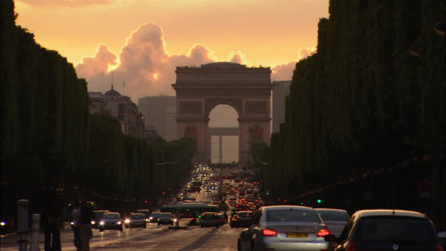 Lockdown of heavy traffic on Champs Elysees in front of Arc de Triomphe at sunset / Paris, France