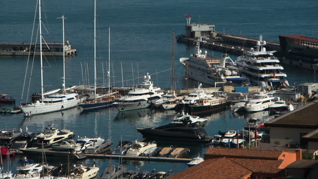 lockdown of several luxury yachts and other boats moored in monte carlo harbor gently swaying in the tide waters - other点の映像素材/bロール