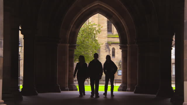 lockdown of three people as they walk through a gothic vaulted archway with a focal blur - glasgow, united kingdom - ceiling stock videos & royalty-free footage