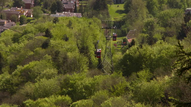 vídeos y material grabado en eventos de stock de lockdown of two gondola cars ascending and descending the cables lines of the luftseilbahn adliswil-felsenegg funicular surrounded by lush green trees and foliage on a bright sunny day  - zurich, switzerland - rodear