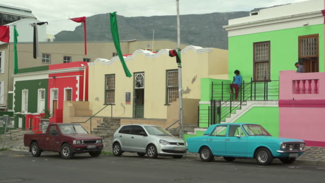 a lockdown of two men looking at their phones while standing in front of brightly painted buildings of bo-kaap near parked cars - cape town, south africa - stationary点の映像素材/bロール