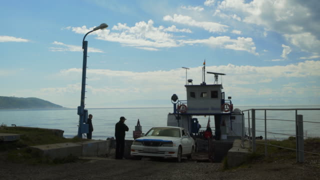 lockdown: old car backing while guided by people to ride the small ferry - lake baikal, russia - ferry ride stock videos & royalty-free footage