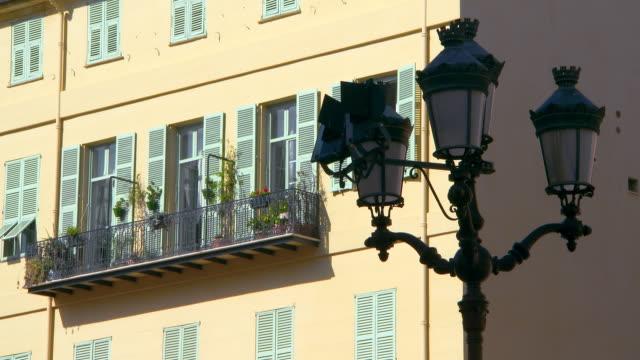 vídeos y material grabado en eventos de stock de lockdown: old lamp post with building in nice france - detalle arquitectónico exterior