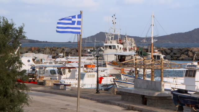 lockdown: picturesque yachts bob at a pier behind a fluttering greek flag - ギリシャ国旗点の映像素材/bロール