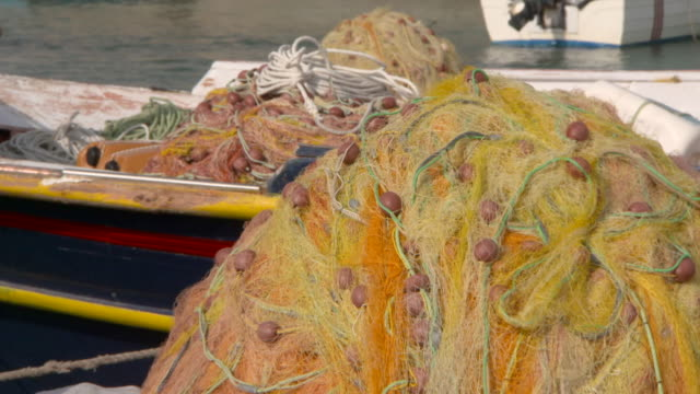 lockdown: piles of fishing nets on a pier and a rocking fishing boat - heap stock videos & royalty-free footage