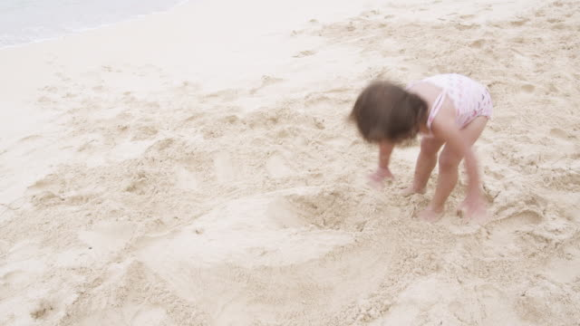 vidéos et rushes de lockdown shot of a young girl playing in the sand on a beach - maillot une pièce