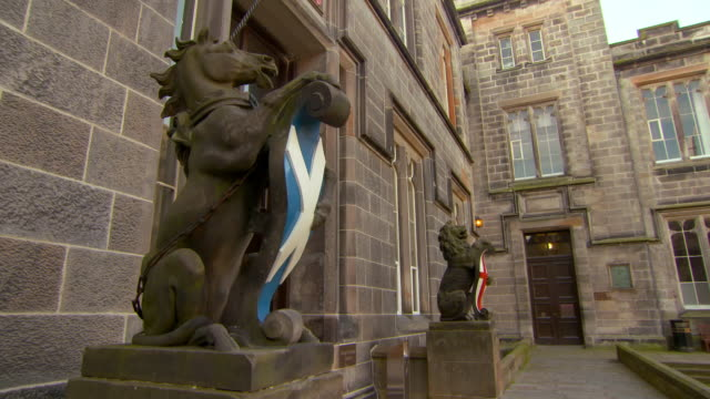 lockdown shot of animal statues with flags against college building in city - aberdeen, scotland - horse family stock videos & royalty-free footage