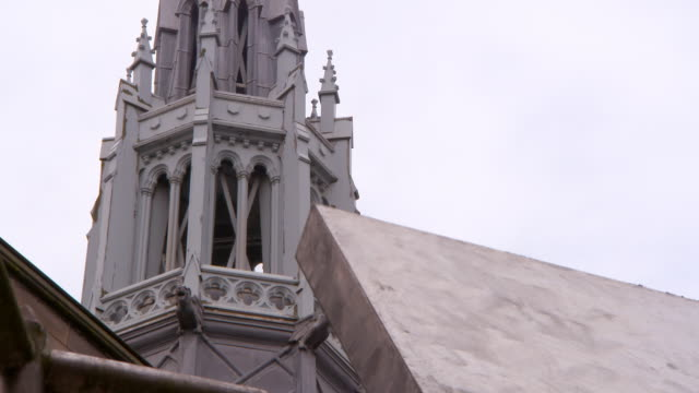 lockdown shot of artwork against public university bell tower in city against sky - glasgow, scotland - religious equipment stock videos & royalty-free footage