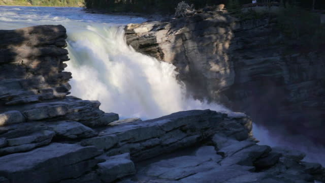 stockvideo's en b-roll-footage met lockdown shot of beautiful waterfall through rocks at famous national park - jasper national park, canada - jasper national park