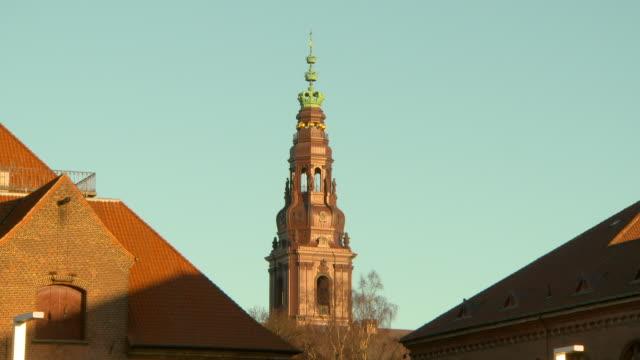 vídeos de stock e filmes b-roll de lockdown shot of bell tower amidst buildings in city against clear sky - copenhagen, denmark - pináculo campanário