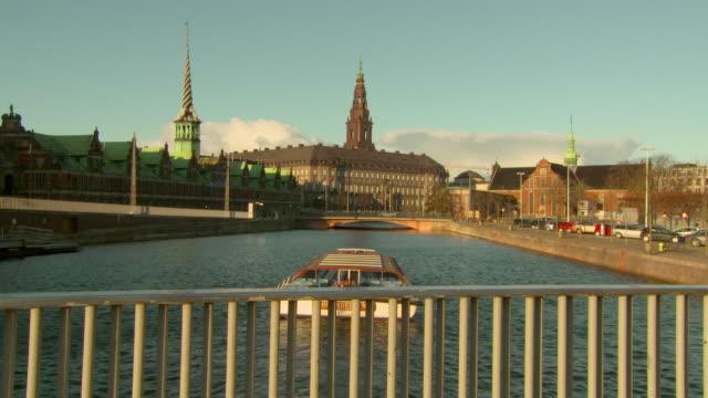 vídeos de stock e filmes b-roll de lockdown shot of boat in canal against landmarks and buildings on sunny day - copenhagen, denmark - pináculo campanário