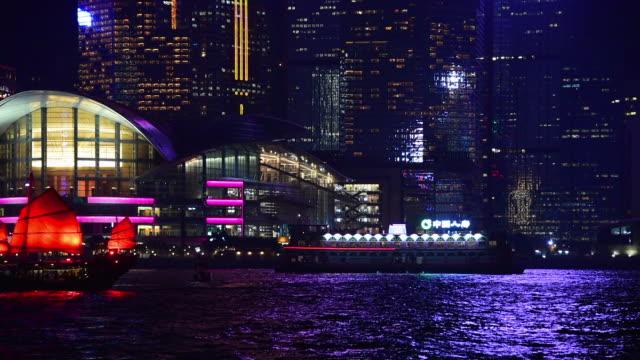 lockdown shot of boats in sea against illuminated modern buildings at night - hong kong, china - hong kong stock videos & royalty-free footage