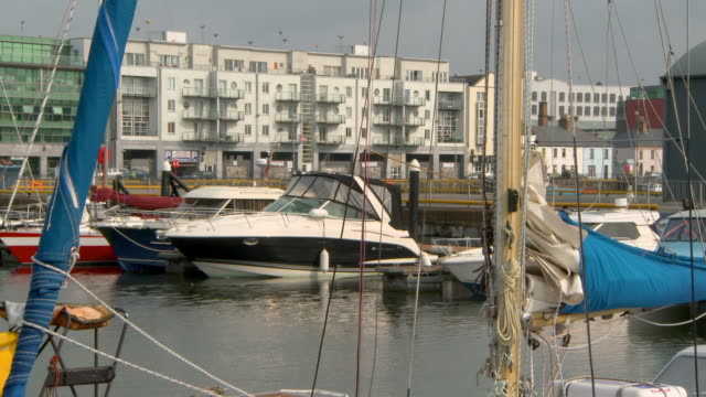 lockdown shot of boats moored at harbor near buildings in city on sunny day - galway, ireland - marina stock videos & royalty-free footage