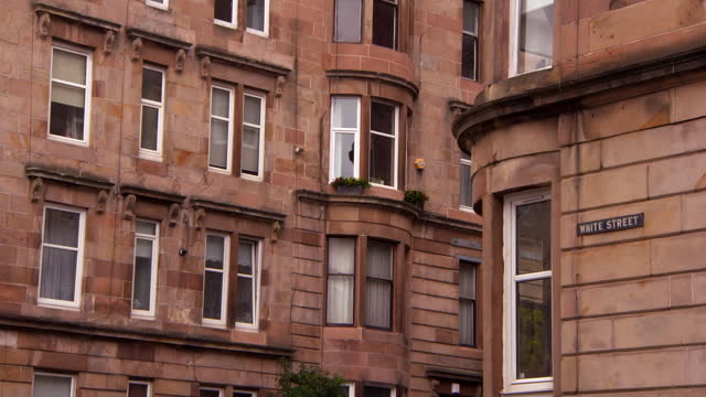 lockdown shot of brown residential buildings with white street sign on wall in city - glasglow, scotland - western script stock videos & royalty-free footage