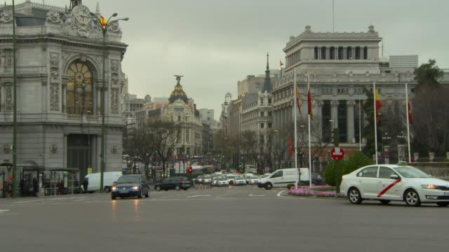 lockdown shot of busy street in city against sky during sunset - madrid, portugal - スペイン国旗点の映像素材/bロール