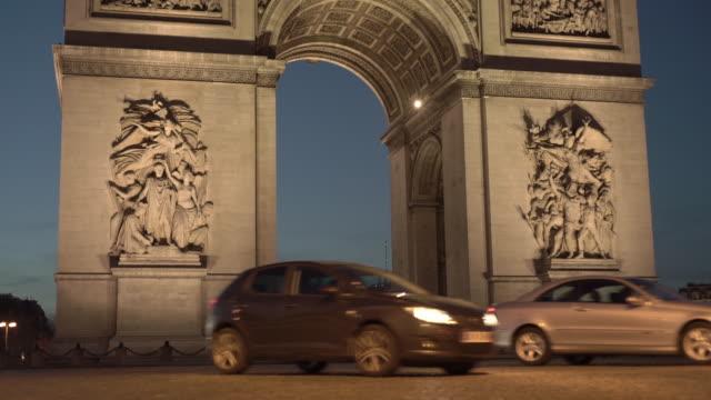 vidéos et rushes de lockdown shot of cars moving across arc de triomphe - arc élément architectural