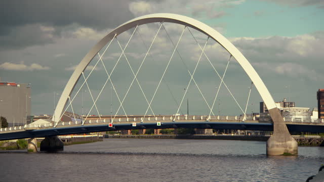 lockdown shot of cars on famous the clyde arc over river clyde in city - glasglow, scotland - cable stayed bridge stock videos & royalty-free footage