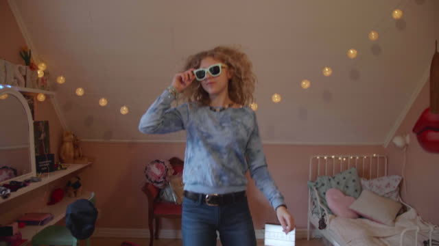 lockdown shot of cheerful girl dancing with sunglasses in bedroom at home - bedroom stock videos & royalty-free footage