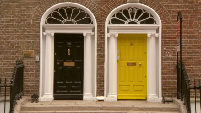 lockdown shot of closed yellow and black doors on brick wall in city - dublin, ireland - yellow stock videos & royalty-free footage