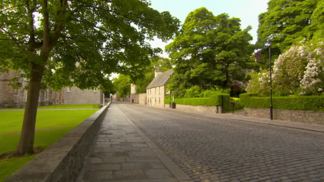 lockdown shot of cobblestone street amidst buildings and trees in city - aberdeen, scotland - aberdeen schottland stock-videos und b-roll-filmmaterial