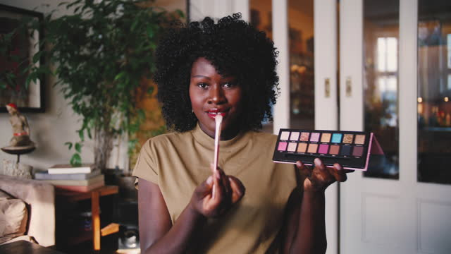 Lockdown shot of confident mature female influencer holding palette while making eyeshadow tutorial at home