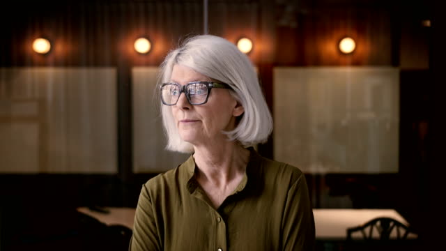 lockdown shot of confident senior businesswoman nodding head in office - senior women stock videos & royalty-free footage