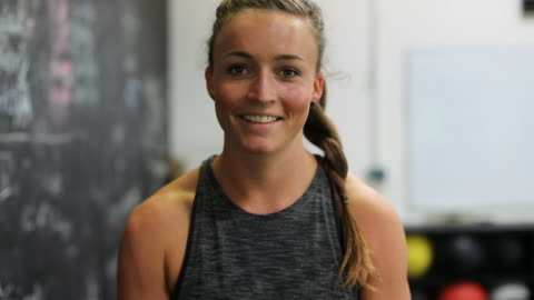 lockdown shot of confident woman smiling in gym - braided hair stock videos & royalty-free footage
