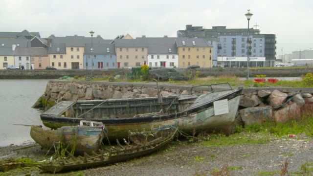 lockdown shot of damaged boats moored on shore in sea near buildings against sky - galway, ireland - moored stock videos & royalty-free footage