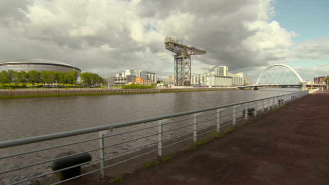 lockdown shot of famous cable-stayed bridge over river clyde in city against cloudy sky - glasgow, scotland - cable stayed bridge stock videos & royalty-free footage