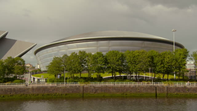lockdown shot of famous indoor arena building near river clyde in city against sky on sunny day - glasgow, scotland - auditorium stock videos & royalty-free footage
