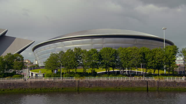 lockdown shot of famous the sse hydro by river clyde in city against sky on sunny day - glasglow, scotland - waterfront stock videos & royalty-free footage
